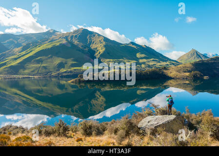 Hiker standing on rocks, mountains reflecting in lake, Moke Lake near Queenstown, Otago Region, Southland, New Zealand - Stock Photo