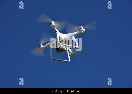 A view from below of a flying DJI Phantom 4 Drone  with a gimbal and camera attached.  Drone, photography, video, - Stock Photo
