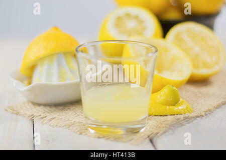 A glass of squeezed lemon juice and lemons around. - Stock Photo