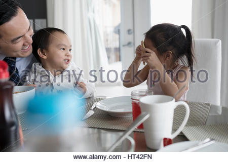 Playful father and children at breakfast table - Stock Photo