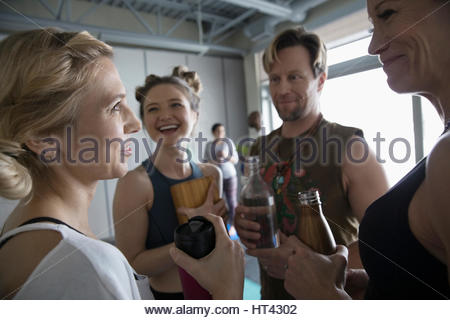 Smiling friends with water bottles talking after yoga class - Stock Photo