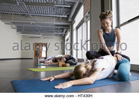 Yoga teacher adjusting hips of woman practicing yoga childs pose in yoga class studio - Stock Photo