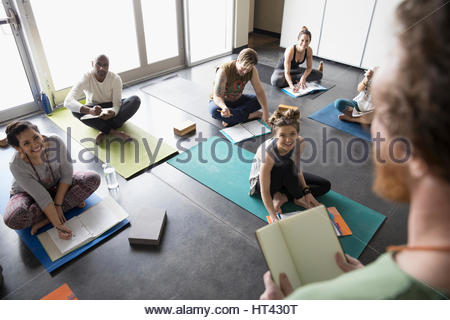 Yoga teacher talking to students with journals on yoga mats in yoga class studio - Stock Photo