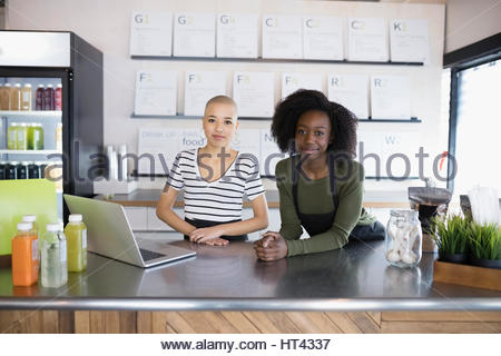 Portrait confident young women working at laptop in juice bar - Stock Photo