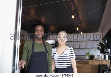 Portrait smiling young women standing in juice bar doorway - Stock Photo