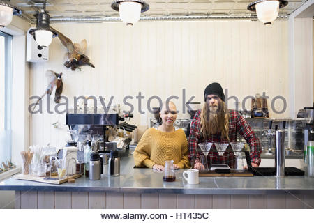 Portrait confident baristas working in cafe - Stock Photo