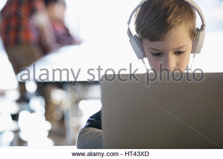 Focused pre-adolescent  boy wearing headphones listening to music at laptop - Stock Photo