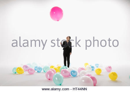 Businesswoman holding large pink balloon against white background - Stock Photo