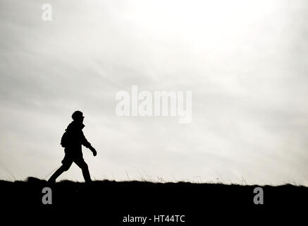 Silhouette of a woman walking a dog on a cloudy day - Stock Photo