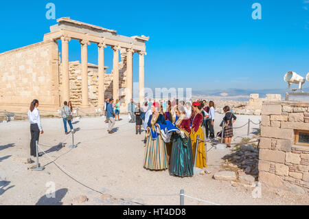ATHENS, GREECE - OCTOBER 12, 2013: The women in national Greek costumes on teritory of Parthenon next to the Erechtheion, - Stock Photo