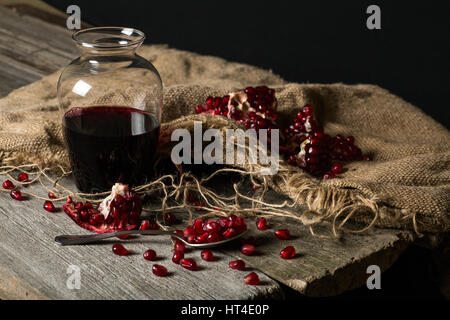 Carafe with pomegranate juice, seeds with a spoon on a wooden table. Stock Photo