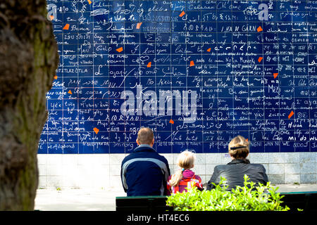 Family sitting in front of love wall in Paris. - Stock Photo