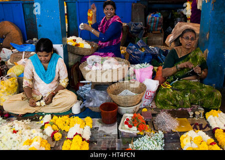 Women selling flowers at the Mapusa Market in North Goa, India. People from the surrounding come to Mapusa to sell - Stock Photo