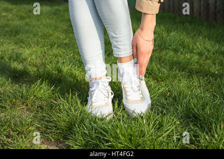 Slender female legs in jeans and white sneakers on a green lawn on a sunny day - Stock Photo