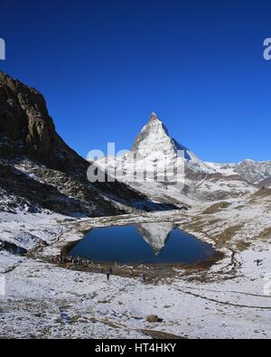 Matterhorn mirroring in lake Riffelsee. Autumn day in the Swiss Alps. - Stock Photo