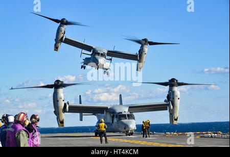 A U.S. Marine Corps MV-22 Osprey aircraft launches from the flight deck aboard the USN Wasp-class amphibious assault - Stock Photo