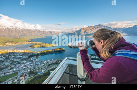 Woman looking through telescope, View of Lake Wakatipu and Queenstown from the Skyline Gondola, gondola cableway - Stock Photo