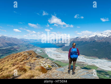Hiker overlooking Lake Wakatipu from Mount Alfred, Glenorchy at Queenstown, Southern Alps, Otago, Southland, New - Stock Photo