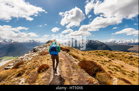 Hiker on a hiking trail, Mount Alfred, Glenorchy at Queenstown, Southern Alps, Otago, Southland, New Zealand - Stock Photo