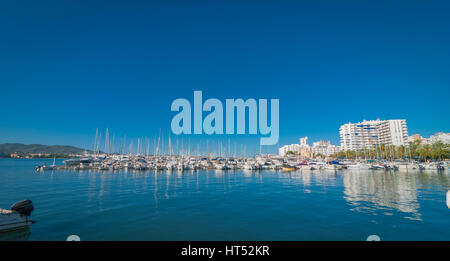Boats, small yachts and water craft of all size in Ibiza marina harbour.  Bright white City of  St Antoni de Portmany. - Stock Photo