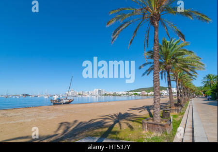 Mid morning sun, along beach sees an abandoned sailboat.  Rows of palm trees line water's edge in Ibiza, St Antoni - Stock Photo
