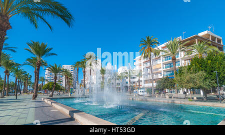 Bright morning sunshine on town square pedestrian park & fountain.  Hotels in background.  Lovely Fountain park - Stock Photo