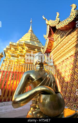 Golden buddha statue and pagoda against clear blue sky at Wat Phra That Doi Suthep, A famous Theravada buddhist - Stock Photo