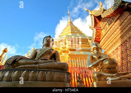 Buddha statues and golden pagoda against clear blue sky at Wat Phra That Doi Suthep, A famous Theravada buddhist - Stock Photo