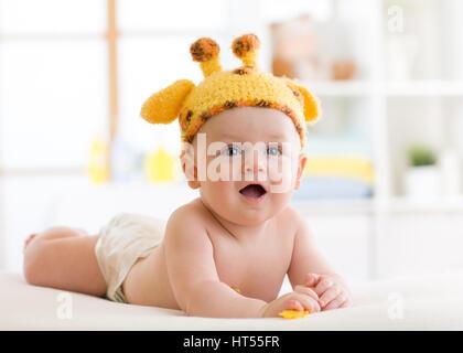 Baby boy in funny giraffe hat lying on his belly in nursery - Stock Photo