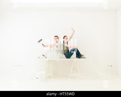 young couple resting after painting their home-office - Stock Photo