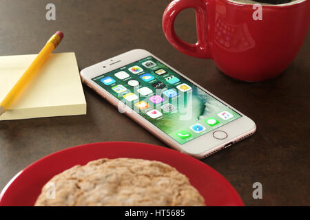 Koszalin, Poland – March 07, 2017: Pink iPhone 7 on stone table. Coffee break. Devices displaying the applications - Stock Photo