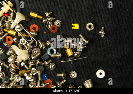 techno backgrounds - various bolts, screws, washers, nuts and other computer small fasteners on black fabric - Stock Photo