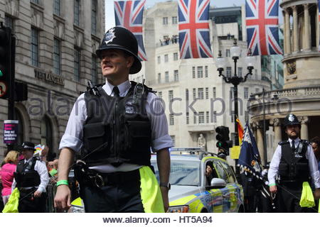 A British police officer smiles as he participates in the 2016 London Pride festival Credit: reallifephotos / Alamy - Stock Photo