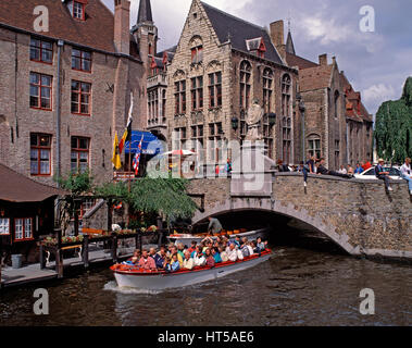 Tourist boat passing under a bridge over the Dijver Canal, Bruges, Belgium. - Stock Photo