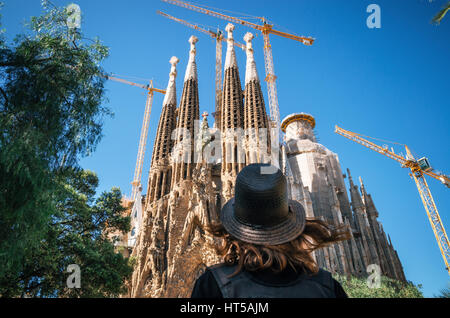 Young woman traveler in a hat looks at the Sagrada Familia the most famous tourist attraction of Barcelona, Catalonia - Stock Photo