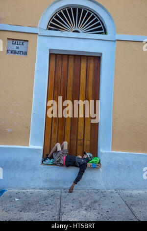 MAN LYING IN WINDOW COLORFUL PAINTED BUILDING CALLE SAN SEBASTIAN OLD SAN JUAN PUERTO RICO - Stock Photo