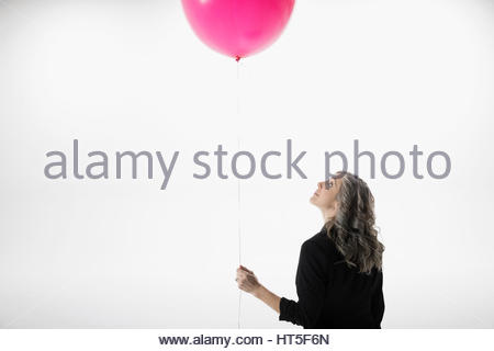 Woman holding and looking up at pink balloon against white background - Stock Photo