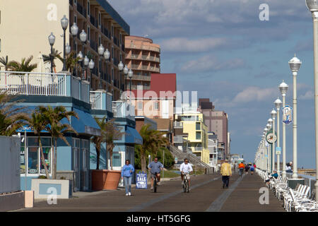 Ocean City, Maryland, USA - October 26, 2016:  Tourists walk and bike along the boardwalk, a popular vacation destination - Stock Photo