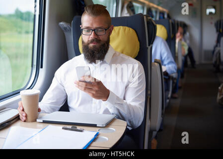 Businessman working on the train - Stock Photo