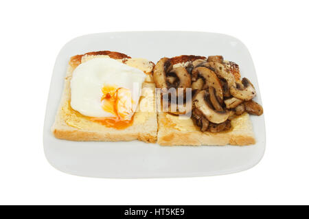 Poached egg and sliced seasoned mushrooms with buttered toast on a plate isolated against white - Stock Photo