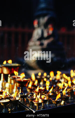 Oil lamps burning in the temple - Stock Photo
