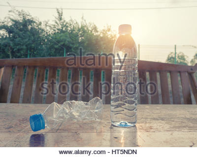 Plastic water bottles with water and no water on dry wood. - Stock Photo