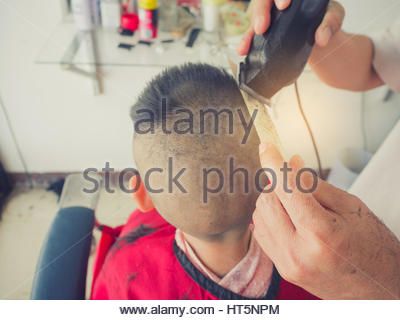 Little boy getting haircut by barber. - Stock Photo