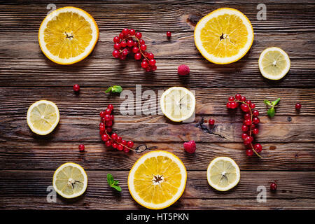 Lemon and orange rings, red currants, raspberries and mint leaves on wooden background. Table top view. Fresh fruit - Stock Photo