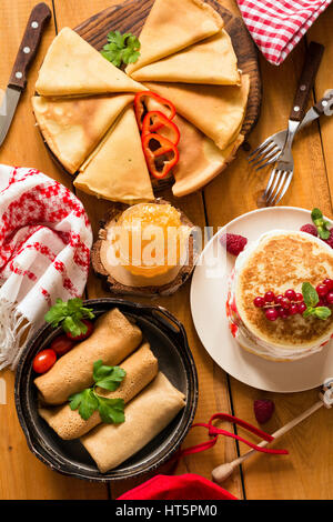 Various types of crepes and pancakes on rustic wooden table, top view - Stock Photo