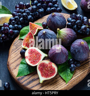 Fresh black grapes, lemons and purple figs on wooden cutting board sprinkled with water. Still life of fresh fruits. - Stock Photo