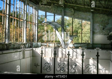 Abandoned swimming pool in Pripyat, the ghost town in the Chernobyl Exclusion Zone - Stock Photo