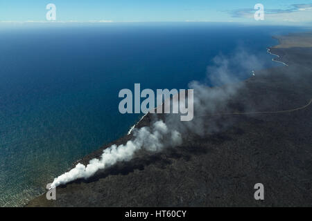 Volcanic gases and steam at Kamokuna lava entry on the Big Island of Hawaii. View from above showing solidified - Stock Photo