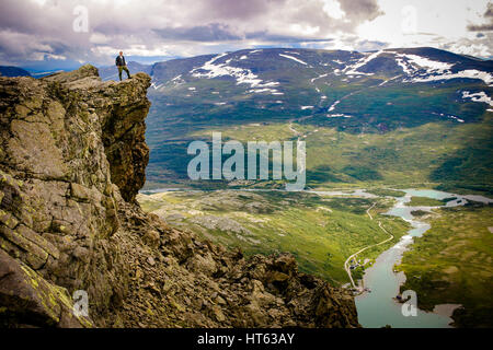 Man standing at edge of cliff at Mount Besseggen, Norway - Stock Photo