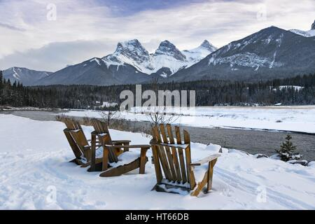 Adirondack Chairs in Winter on Bow River in Canmore, Alberta looking to Three Sisters Snowy Mountain Tops near Banff National Park in Canadian Rockies